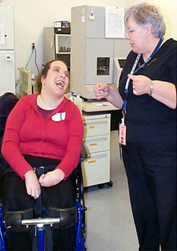 Young woman in a wheelchair laughing with a coworker in the office